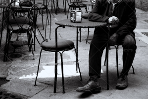 Well Dressed Man Sits Outside At Cafe In Old Italian Alley