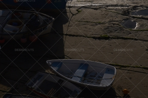 Boats Lined Up On The Shore Of A Glistening Beach In Cornwall