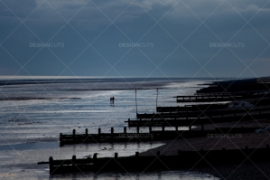 Couple On Morning Walk By Groynes On British Seaside