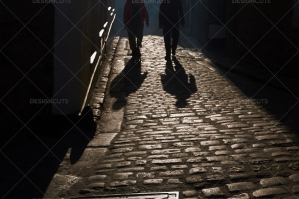 Two People Walking Through Backlit Streets