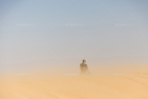 A Sahrawi Woman Wearing A Traditional Dress Disappearing Into A Sandstorm