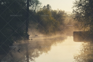 Morning Mist Above The River With Reflection Of Trees On Surface Of The Water