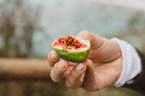 Woman Holding Half Of A Fig In Her Hand
